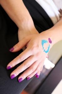 Pretty glitter tattoo matches purple manicure